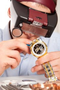 watchmaker removing back of watch to reveal battery